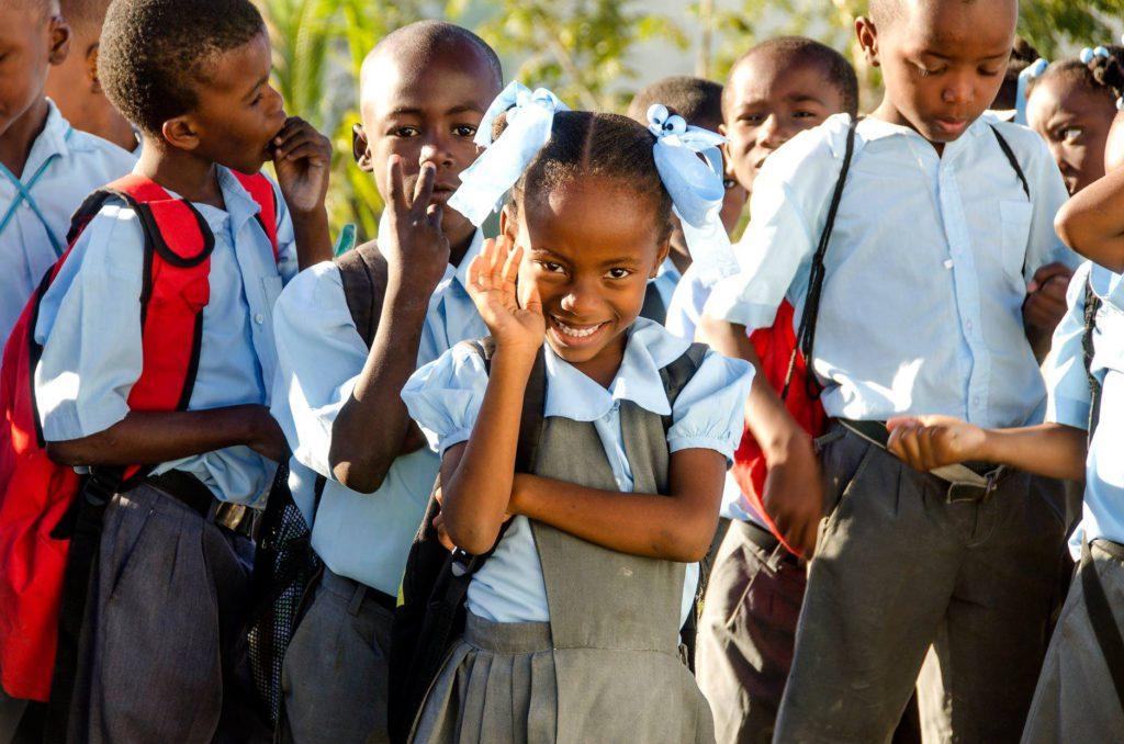 kinderen uit Haïti zeggen hallo in hun school uniform
