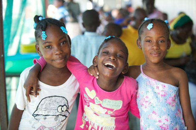 Drie meisjes uit Haiti die lachen